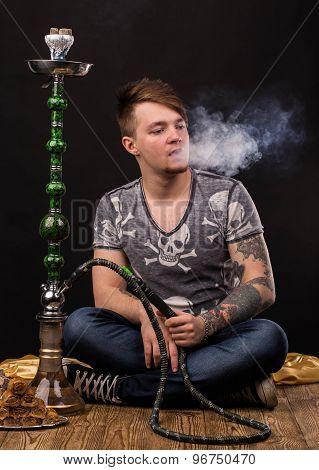 Tattooed man smoking traditional hookah.