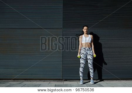 Attractive woman holding weights with hands by sides while standing black copy space background
