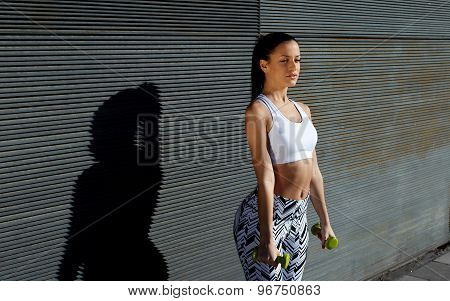 Attractive young female look to you while working on her arms outdoors against copy space