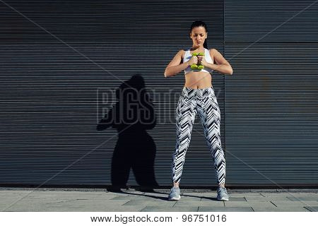 Confident sporty woman using dumbbells to work out her arms while training outdoors