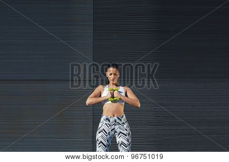 Gorgeous woman in workout gear holding weights with her hands together while training outdoors