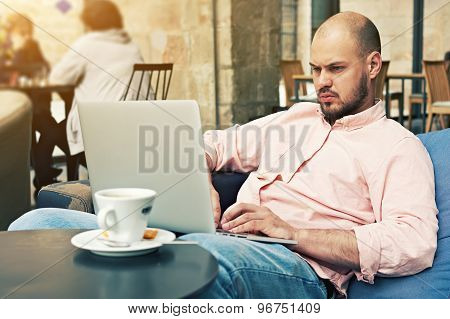 Successful businessman sitting on sofa front open laptop computer and cup of coffee or tea
