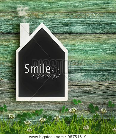 House shaped chalkboard on wood background