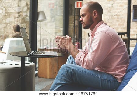 Male student working with laptop compute while holding cup of coffee in modern university hall