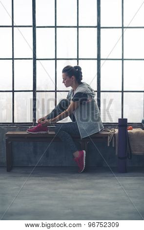 Fit Woman Sitting In Profile In City Loft Gym Tying Shoe