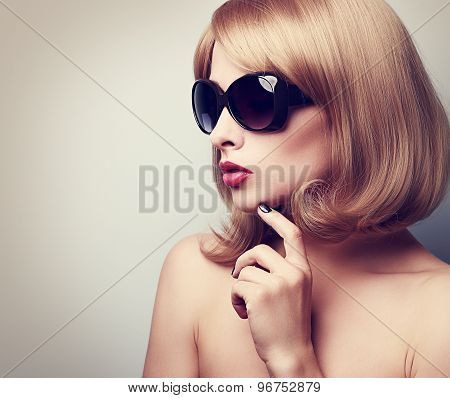 Female Model Profile In Fashion Sunglasses With Blond Short Hair Style And Finger Near Face