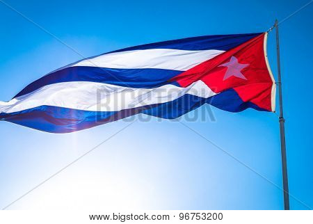 The flag of Cuba waving in the wind against a blue sky