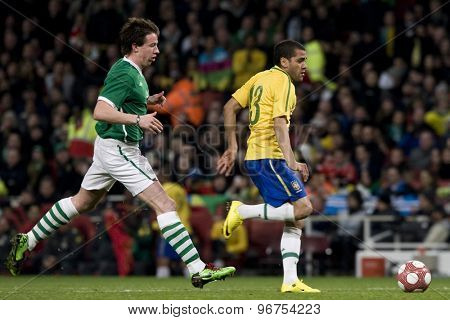 LONDON, ENGLAND. March 02 2010: Ireland's Sean St Ledger and Brazil's Daniel Alves during the international football friendly between Brazil and the Republic of Ireland played at the Emirates Stadium.