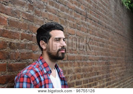 Portrait Of Latin Man Against A Brick Wall.