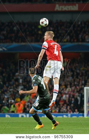 LONDON, ENGLAND - Oct 01 2013: Arsenal's defender Per Mertesacker from Germany  heads the ball during the UEFA Champions League match between Arsenal and Napoli.
