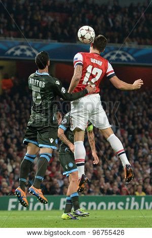LONDON, ENGLAND - Oct 01 2013: Napoli's defender Miguel Angel Britos and Arsenal's forward Olivier Giroud compete for the ball during the UEFA Champions League match between Arsenal and Napoli.