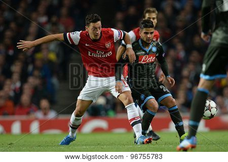 LONDON, ENGLAND - Oct 01 2013: Arsenal's midfielder Mesut Ozil from Germany and Napoli's forward Lorenzo Insigne compete for the ball during the UEFA Champions League match between Arsenal and Napoli.