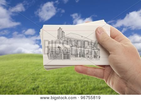 Male Hand Holding Stack of Paper With House Drawing Over Empty Grass Field and Sky.
