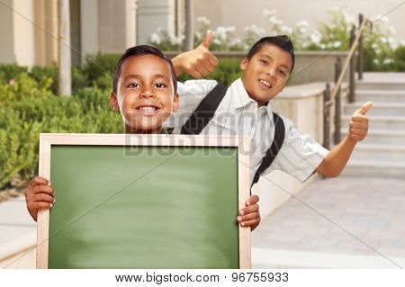 Happy Hispanic Boys with Thumbs Up Holding Blank Chalk Board Outside on School Campus.