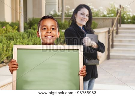 Happy Hispanic Boy Holding Blank Chalk Board on Campus As Teacher Looks on From Behind.