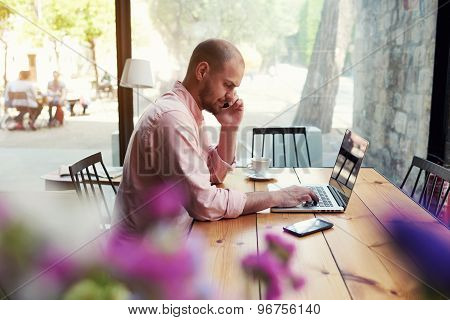 Business man use laptop sitting at wooden table of modern coffee shop while talking on smart phone