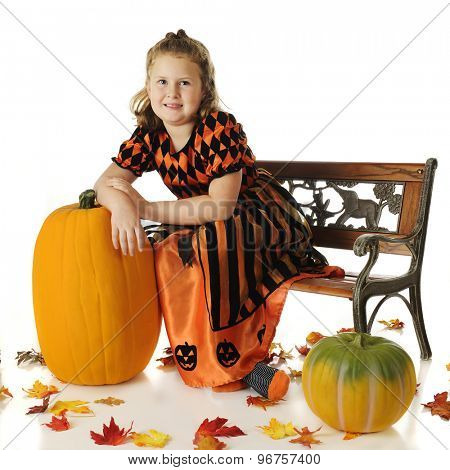 An elementary girl in a beautiful Halloween dress, leaning on a tall pumpkin surrounded with colorful fallen leaves.  On a white background.
