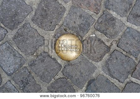 VERONA, ITALY - JULY 13: Detail of street bolt on stone road with the City of Verona crest. July 13, 2015 in Verona.