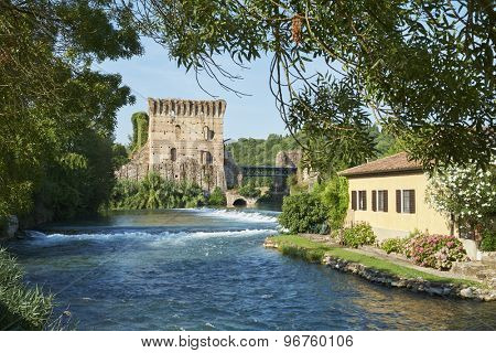 BORGHETTO, ITALY - JULY 11: Ruin of tower at Visconteo bridge, framed by vegetation and coasted by river Mincio. July 11, 2015 in Borghetto.
