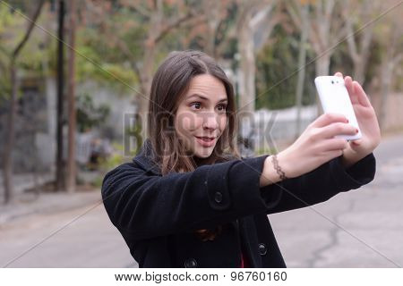 Latin Woman Taking A Selfie With Her Cellphone
