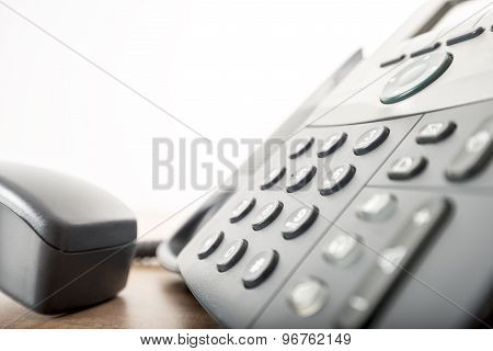 Close Up Angled View Of A Black Landline Telephone With A Number Pad And The Handset Or Receiver Off