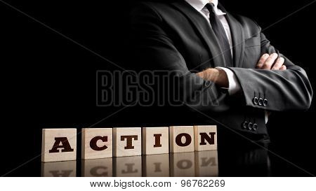 Businessman In A Strong Confident Pose Standing Next To Six Wooden Cubes Spelling Action