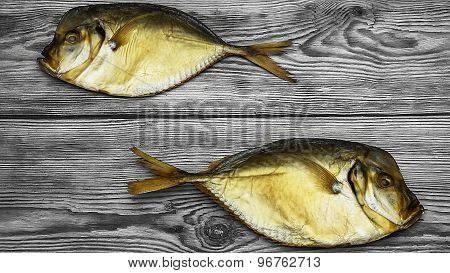 Two Smoked Fish On The Wooden Table Closeup