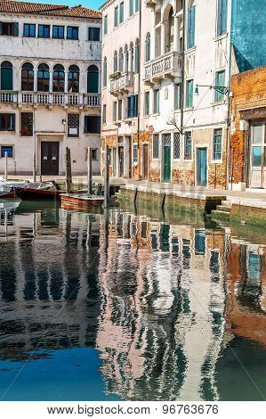 Reflection Of Buildings In Water Canal In Venice