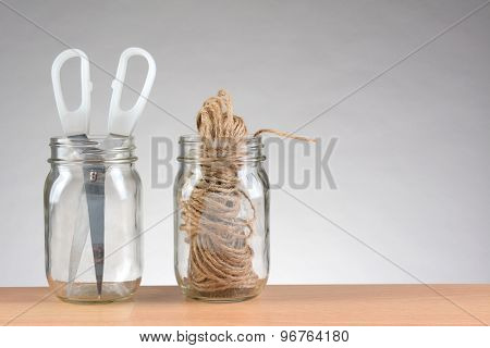 Closeup of two jars with string and scissors for wrapping packages. Horizontal format on a wood desk top against a light to dark gray background with copy space.