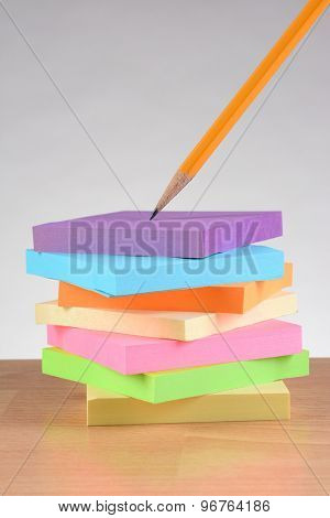 Colorful note pads and pencil on teachers desk. Vertical format against a light to dark gray background.