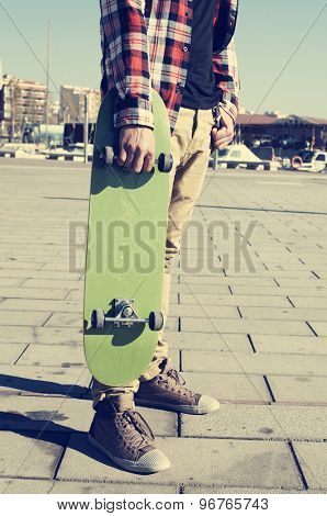 young caucasian man wearing a plaid shirt holds a green skateboard in his hand
