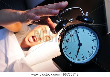 young caucasian man in bed yawns while stops the alarm clock at 7 in the morning