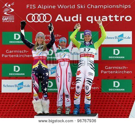 GARMISCH PARTENKIRCHEN, GERMANY. Feb 13 2011: Lindsey Vonn (USA) (L) 2nd Elisabeth Goergl (AUT) (C) winner and Maria Riesch (GER)(r) 3rd on the podium of the women's downhill race