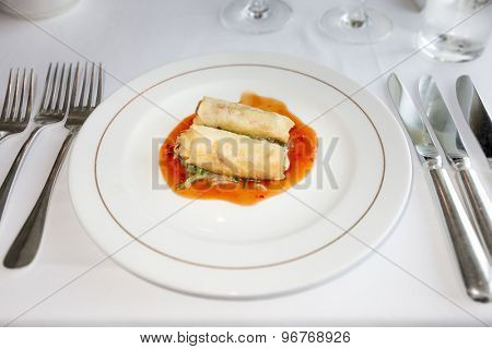 An image of two spring rolls on hot sauce