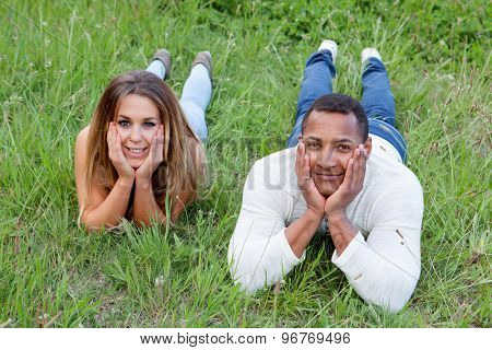 Happy couple lying on the grass in the field thinking about his future