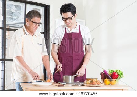 Asian senior father and adult son cooking meal at kitchen. Family living lifestyle at home.