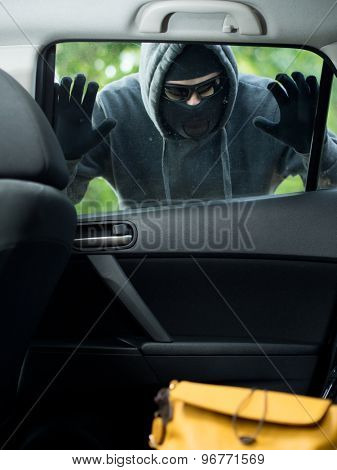 Transportation crime concept .Thief stealing bag from the car