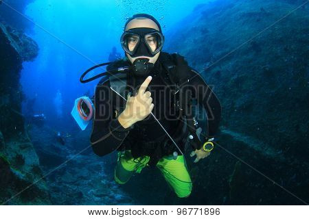 Scuba diver having fun exploring reef and caves