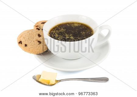 Black coffee with added butter and cookies served in cup and saucer