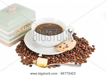 Black coffee with added butter and cookie served in cup and saucer