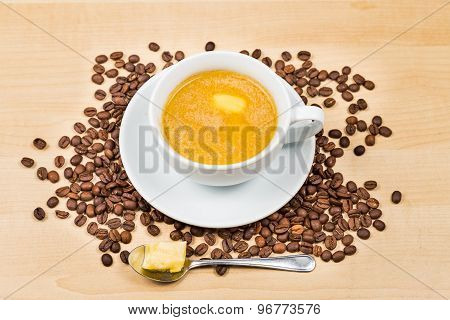 Coffee with added milk and butter served on cup and saucer