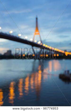 Abstract blurred bokeh light, suspension bridge with water reflection