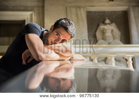 Young Man Resting with Head on Staircase Railing