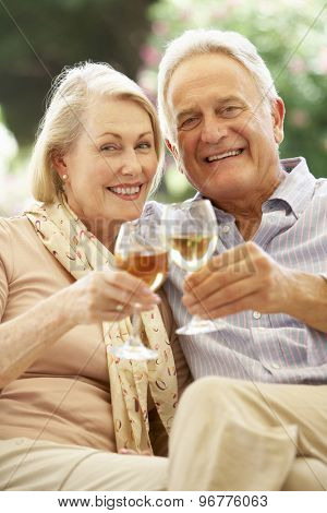 Portrait Of Senior Couple Relaxing On Sofa With Glass Of Wine