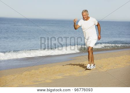 Senior Man Jogging Along Beach