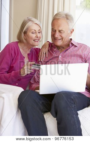 Senior Couple Using Laptop For Online Purchase At Home