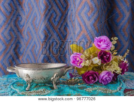 Moroccan Metal Bowl Placed On A Table With Flowers.