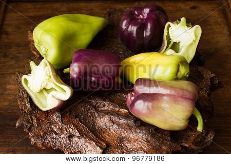 Purple And Green Pepper On A Wooden Background