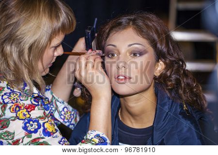 young beautiful woman applying powder on cheek with brush