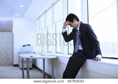 Depressed young business man sitting in office